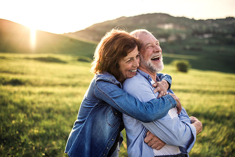 Happy couple hugging in field