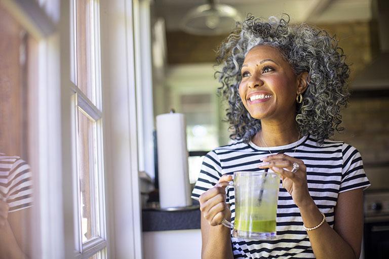 Women drinking juice by window